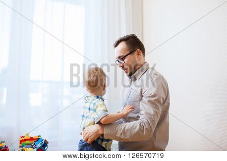 family, parenthood, fatherhood, care and people concept - father taking care of little son at home
