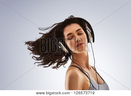 beautiful young woman listening music in headphones on a gray background. the girl is resting and enjoys the music.