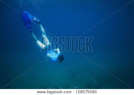 The boy in flippers dove into the sea and swims to the bottom among the fish