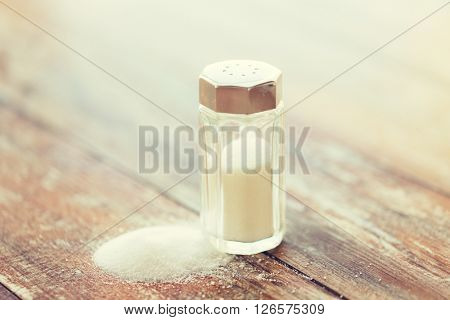 food, junk-food, cooking and unhealthy eating concept - close up of white salt cellar on wooden table