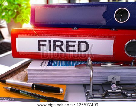 Red Ring Binder with Inscription Fired on Background of Working Table with Office Supplies and Laptop. Fired - Toned Illustration. Fired Business Concept on Blurred Background. 3D Render.