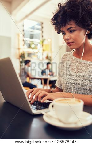 Portrait of attractive young woman with earphones working on laptop at a cafe. African female at a coffee shop surfing internet on laptop.
