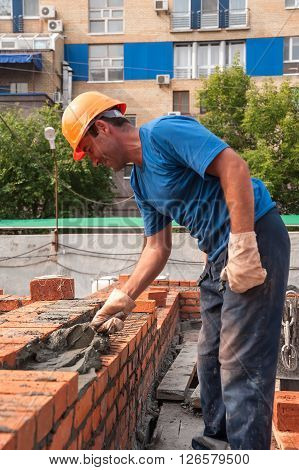 Tyumen, Russia - July 31, 2013: JSC Mostostroy-11. Construction of 18 floor brick residental house at the intersection of streets of Nemtsov and Tsiolkovsky. Bricklayer on house constructionwork