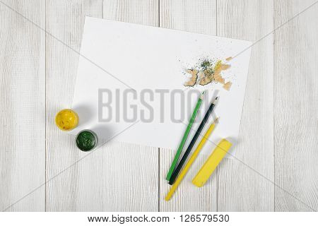 Work place of designer with colored pencils, brush, gouache jars,  colored chalks and a white paper in top view. Art disposition on wooden surface.