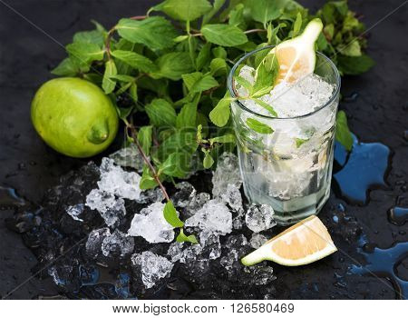 Mojito mixing set. Bunch of fresh mint, lime, chipped ice and cocktail glass over black slate stone backdrop, selective focus. ** Note: Shallow depth of field
