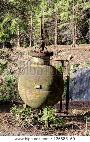 Old unused rusty pressure vessel by the forest