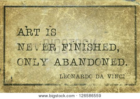 Art is never finished only abandoned - ancient Italian artist Leonardo da Vinci quote printed on grunge vintage cardboard