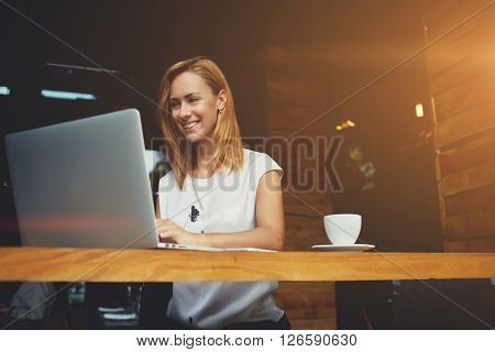 Pretty female student with cute smile keyboarding something on net-book while relaxing after lectures in University beautiful happy woman working on laptop computer during coffee break in cafe bar