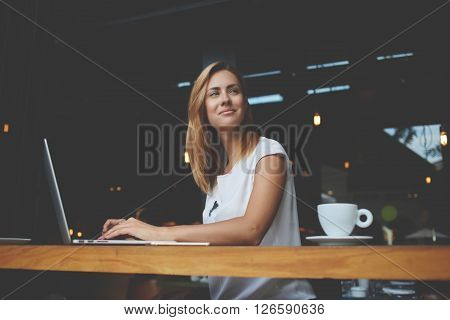 Young gorgeous European woman with pretty face thinking about something while sitting with laptop computer in cafe bar dreamy beautiful female using portable net-book during work break in coffee shop