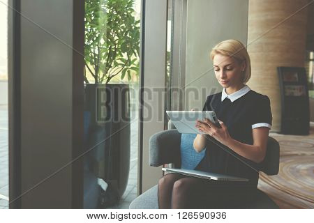 Young successful Caucasian businesswoman is searching needed information for meeting with partners via digital tablet while is sitting with closed laptop computer in modern coffee shop interior