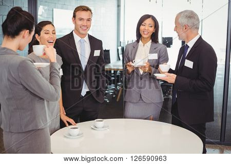 Businesspeople having tea and interacting during breaktime in office