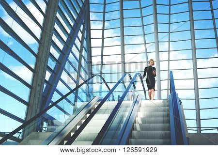 Young businesswoman is searching information on website via cell telephonewhile is standing near escalator staircase in modern airport interior with contemporary building design Copy space background