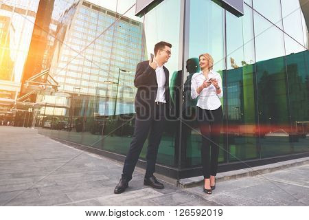 Two smiling business workers with mobile phone in hands are having pleasant conversation before their joint presentation. Cheerful man and woman skilled financiers is talking during break at job