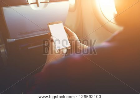 Closeup of man`s hands is holding mobile phone with empty copy space screen for your advertising text message or content.Hipster guy is reading electronic book on cell telephone during flying in plane