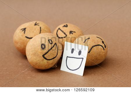 One of brown ball in a group of four look sad and depressed but concealing the emotion hiding behind smiling mask. The others are smiling and laughing. Concept of mental illness, discrimination,bully.