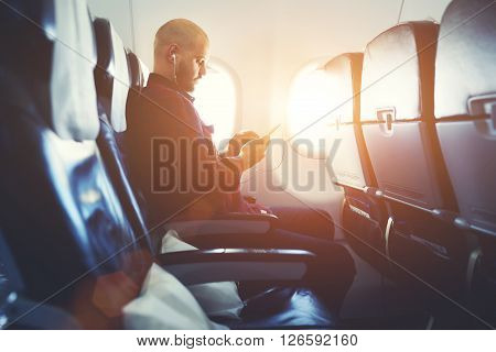 Man entrepreneur is watching video on mobile phone while is sitting in plane near window with sun rays during his business trip. Hipster guy is listening to music in headphones via cell telephone