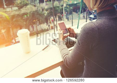 Woman is chatting on mobile phone while is sitting in cafe at the table with digital tablet credit card and take away coffee. Female is booking restaurant for dinner o-nline via cell telephone