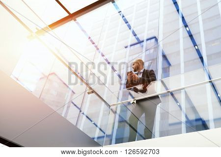 Young man skilled economist in formal wear is holding cell telephone while is standing in modern office interior with contemporary design background with copy space for your advertising text message