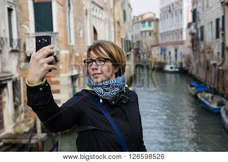 Traveling around the world. European cities. Beautiful modern woman making selfie. Local sights in the background.