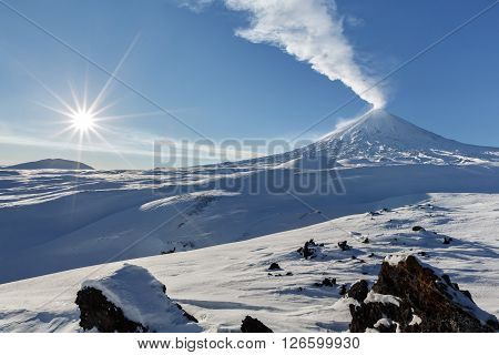 Beautiful volcanic landscape of Kamchatka: winter view of eruption active Klyuchevskaya Sopka (Klyuchevskoy Volcano) - emission from crater of volcano plume of gas steam and ashes. Eurasia Far East Russia Kamchatsky Krai Klyuchevskaya Group of Volcanoes.