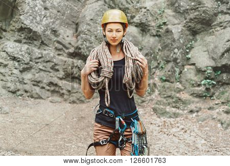 Young woman wearing in safety harness with climber equipment and helmet holding rope and looking at camera on background of rock