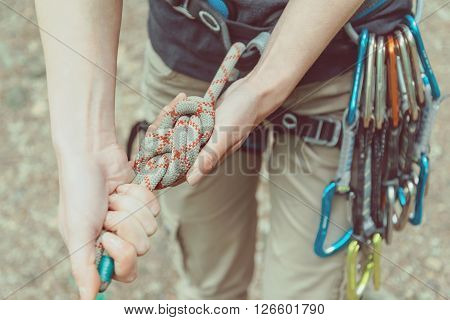 Unrecognizable climber woman wearing in safety harness with quickdraws doing rope eight knot and preparing to climb