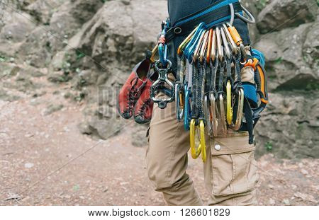 Unrecognizable woman rock climber wearing in safety harness with quickdraws and climbing equipment outdoor
