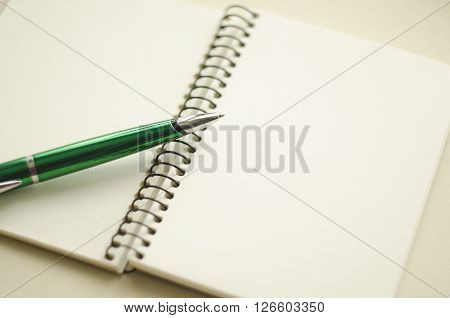 A part of open blank white notebook and green pen on the desk.