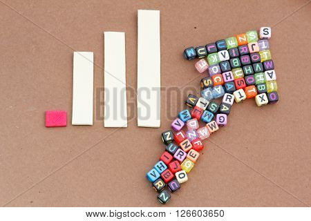 Plastic alphabet block arranged in arrow form with graph beside it showing increasing trend. Concept of growth,economy,statistic,business