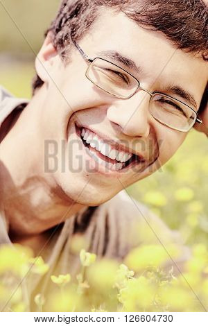 Warm toned close up portrait of young hispanic man wearing glasses, smiling perfect healthy toothy smile in spring park outdoors - humor, dentistry or ophthalmology concept