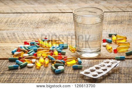 many colorful medical pills and empty pack tablet isolated on wodden table with glass of water