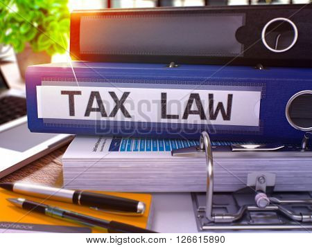 Blue Ring Binder with Inscription Tax Law on Background of Working Table with Office Supplies and Laptop. Tax Law - Toned Illustration. Tax Law Business Concept on Blurred Background. 3D Render.