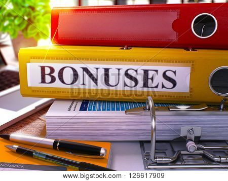 Yellow Ring Binder with Inscription Bonuses on Background of Working Table with Office Supplies and Laptop. Bonuses - Toned Illustration. Bonuses Business Concept on Blurred Background. 3D Render.