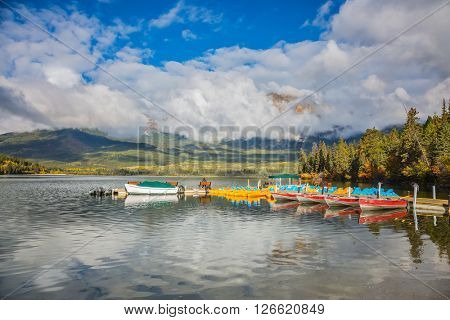 The wooden boat mooring with the moored boats.  On bench of the boat mooring sits elderly woman with camera. Cumulus clouds over the Pyramid mountain and Pyramid Lake