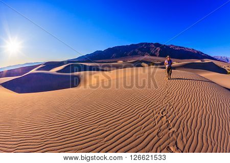 Woman - photographer is among the gently sloping sand dunes. Sunrise in the orange sands of the desert Mesquite Flat, USA