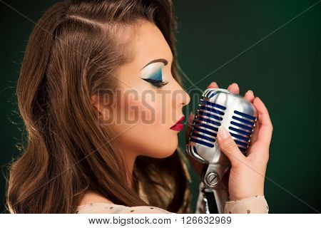 A young pretty woman singer singing ballad with eyes closed and holding a microphone.