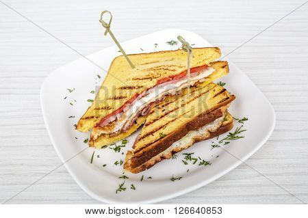sandwich toast grilled with cheese, bacon and salad on white wooden table, background
