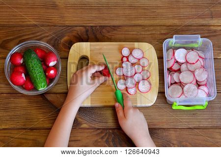 Child cuts radish for salad using kitchen knife. Children hands holding a knife and a radish. Vegetables for salad. Top view