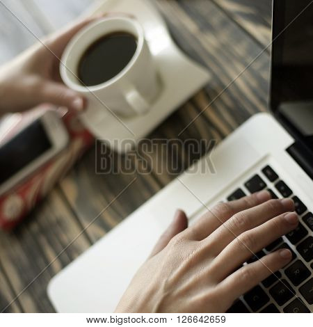 Morning coffee, lap top, mobile phone, female typing and a notepad on desk, artistic soft focus