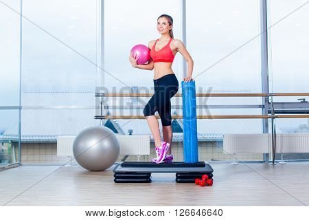 Fitness girl, wearing in sneakers, red top and black  breeches, posing on step board with ball, on the sport equipment background, in the gym. ** Note: Soft Focus at 100%, best at smaller sizes