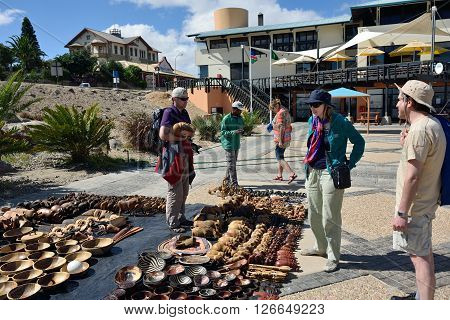 LUDERITZ NAMIBIA - JAN 27 2016: Tourists shown on the craft market in Luderitz. Local hand made toys and other african goods very popular between tourists