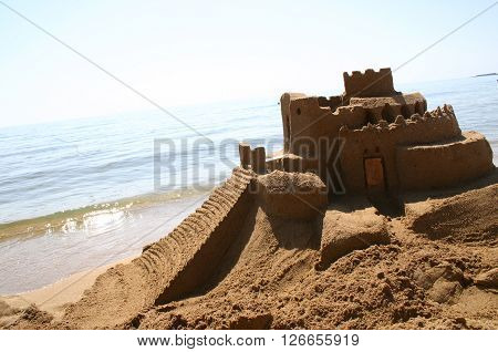 Sand castle from aside on beautiful beach at the ocean