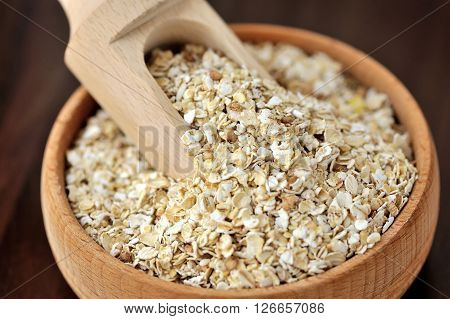 Oatmeal Or Oat Flakes In Bowl And Scoop On Dark Wooden Table