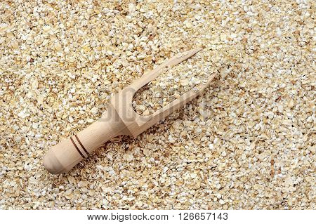 Oat Flakes In Wooden Scoop As Background Or Texture