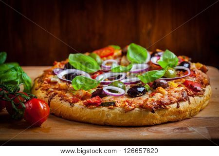 Traditional homemade pizza with tomatoes, olives and basil