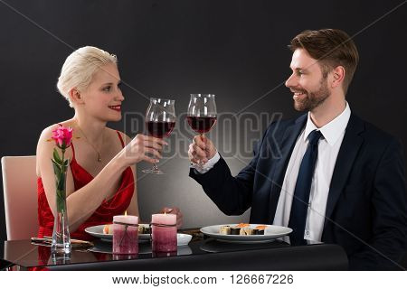 Young Couple Looking At Each Other While Toasting Wineglasses In A Restaurant