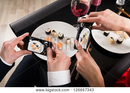 Couple Photographing Food With Smartphones