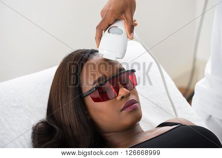 Therapist Giving Laser Epilation Treatment To Woman