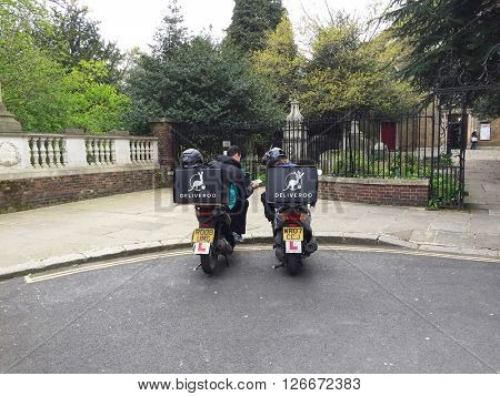 LONDON - APRIL 21: Deliveroo food delivery drivers sit on their scooters waiting for orders on April 21, 2016 in Hampstead, London, UK.