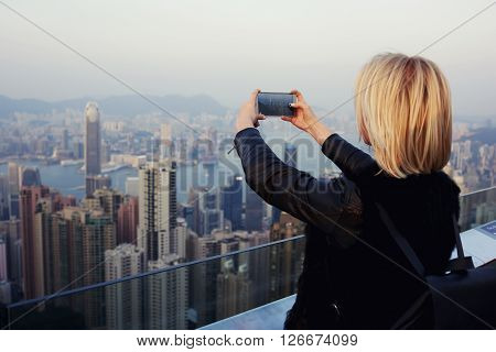 Woman wanderer is taking photo on mobile phone camera of big Hong Kong city while is standing on a roof high building.Hipster girl is shooting video of the view on cell telephone during trip in China